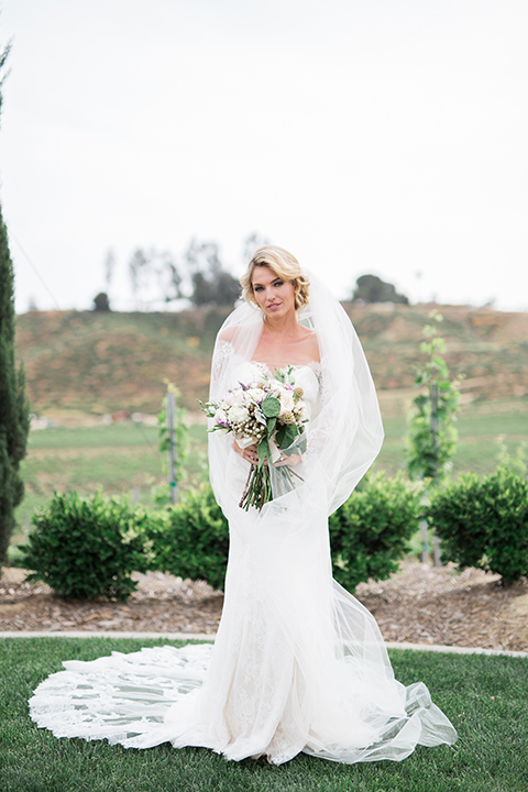temecula-wedding-avensole-winery-bride-lace-gown-with-sleeves-hlding-bouquet-and-veil-ceremony