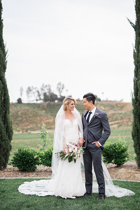 temecula-wedding-avensole-winery-bride-lace-gown-with-sleeves-and-groom-charcoal-tuxedo-with-black-skinny-tie-looking-at-each-other-hugging