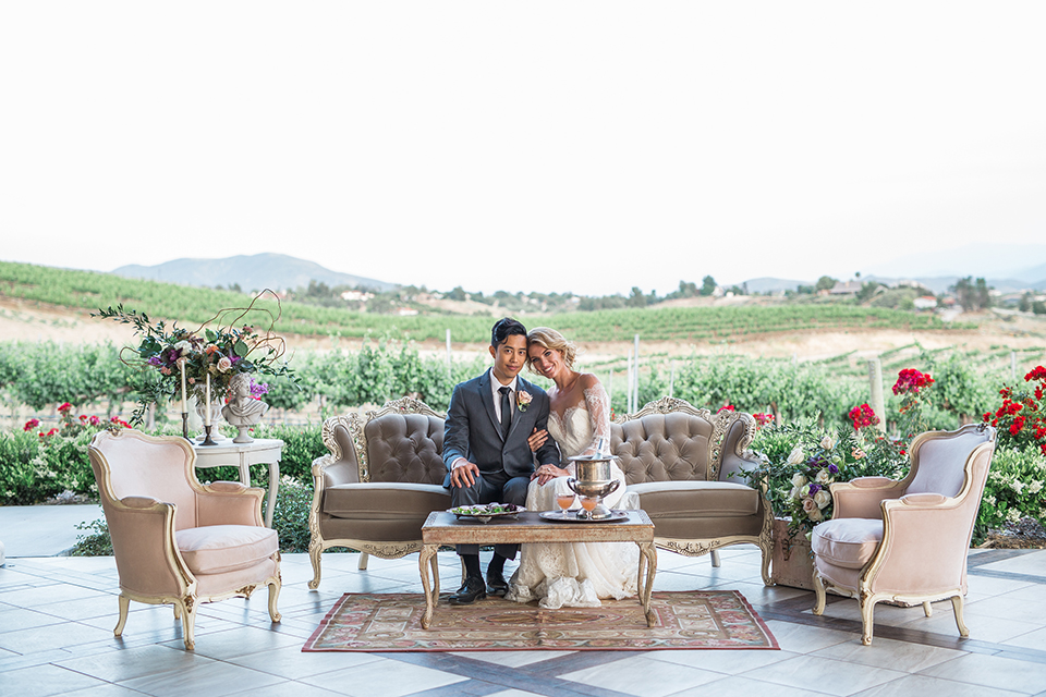 temecula-wedding-avensole-winery-bride-lace-gown-with-sleeves-and-groom-charcoal-tuxedo-with-black-skinny-tie-on-the-couch