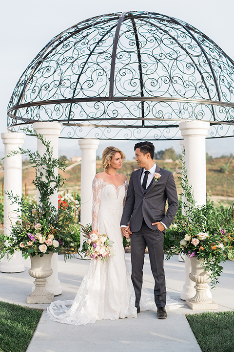 temecula-wedding-avensole-winery-bride-lace-gown-with-sleeves-and-groom-charcoal-tuxedo-with-black-skinny-tie-looking-at-each-other-holding-hands-with-floral-bouquet