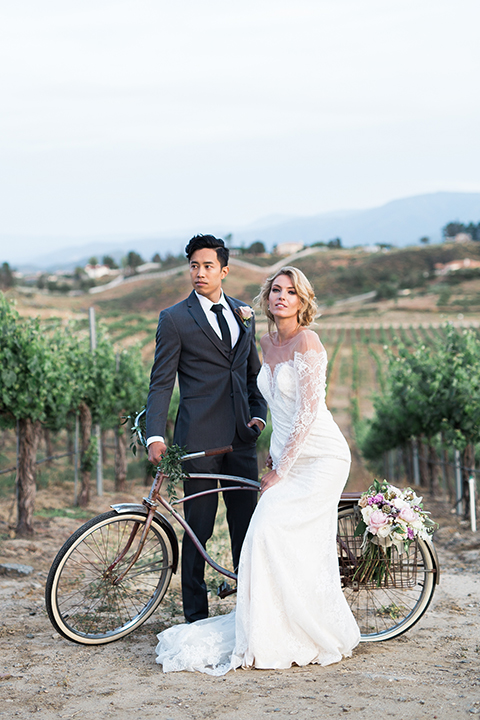 temecula-wedding-avensole-winery-bride-lace-gown-with-sleeves-and-groom-charcoal-tuxedo-with-black-skinny-tie-with-bike