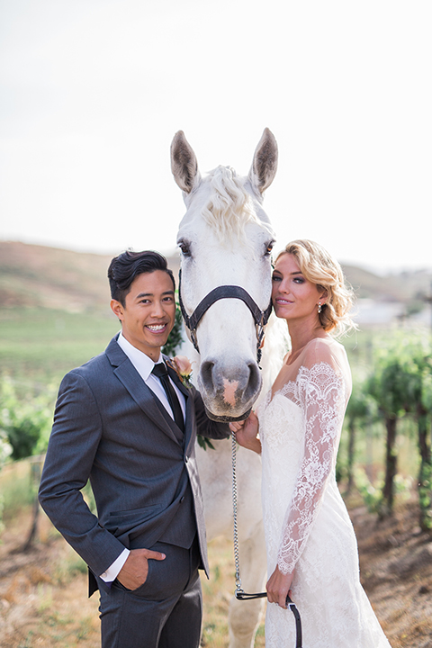 temecula-wedding-avensole-winery-bride-lace-gown-with-sleeves-and-groom-charcoal-tuxedo-with-black-skinny-tie-with-horse-close-up