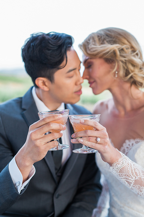 temecula-wedding-avensole-winery-bride-lace-gown-with-sleeves-and-groom-charcoal-tuxedo-with-black-skinny-tie-holding-drinks-touching-heads