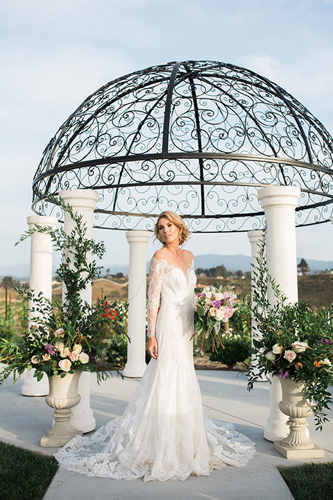temecula-wedding-avensole-winery-bride-lace-gown-with-sleeves-hlding-bouquet-and-veil