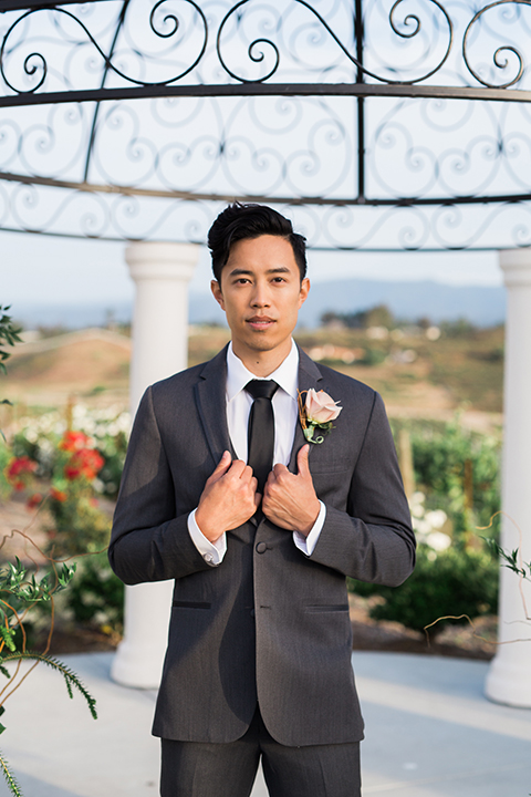 temecula-wedding-avensole-winery-ceremony-groom-charcoal-tuxedo-hands-on-lapel