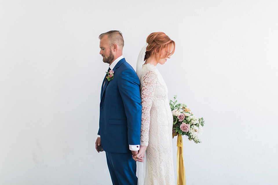 ethereal-shoot-bride-and-groom-back-to-back-bride-wearing-a-flowing-white-gown-with-a-high-neckline-and-long-sleeves-with-lace-detailing-groom-in-cobalt-blue-suit-with-a-black-long-tie