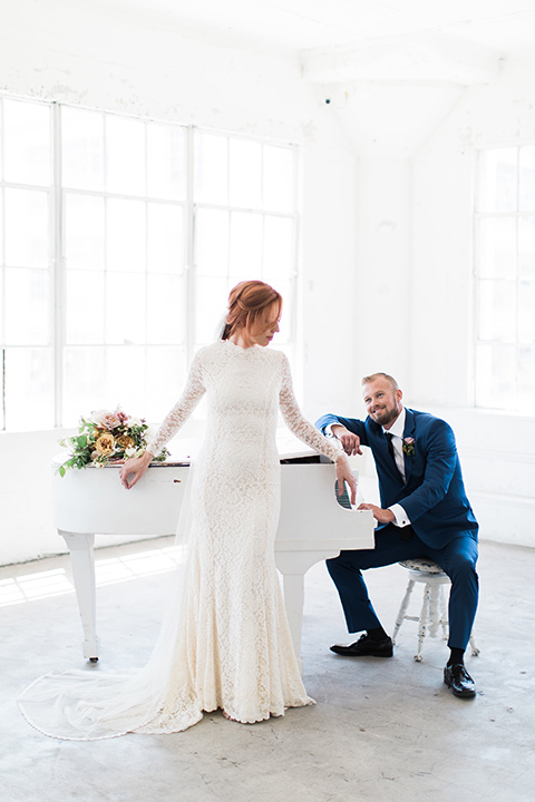 ethereal-shoot-bride-and-groom-by-piano-bride-wearing-a-white-flowing-gown-with-a-high-neckline-and-long-sleeves-with-lace-detailing-groom-in-a-cobalt-suit-with-a-black-long-tie