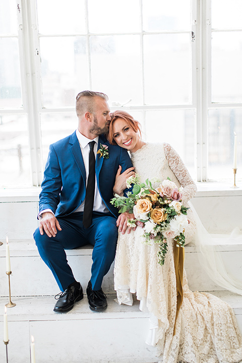 ethereal-shoot-bride-and-groom-by-white-steps-sitting-bride-wearing-a-white-flowing-gown-with-a-high-neckline-and-long-sleeves-with-lace-detailing-groom-in-a-cobalt-suit-with-a-black-long-tie