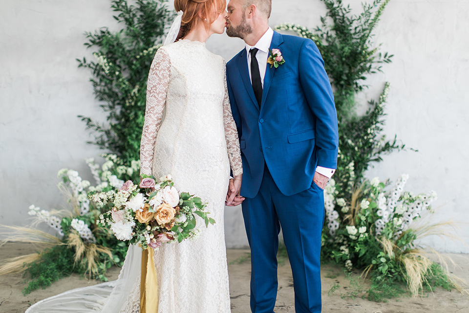 ethereal-shoot-bride-and-groom-ceremony-space-bride-wearing-a-flowing-white-gown-with-a-high-neckline-and-long-sleeves-with-lace-detailing-groom-in-cobalt-blue-suit-with-a-black-long-tie