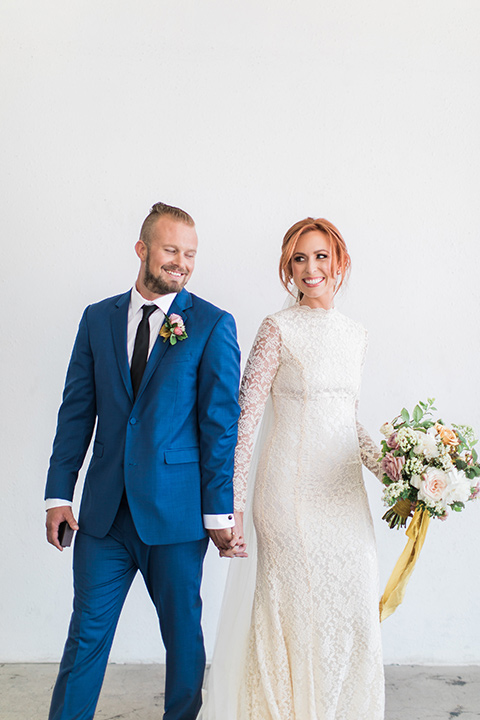 ethereal-shoot-bride-and-groom-holding-hands-bride-wearing-a-white-flowing-gown-with-a-high-neckline-and-long-sleeves-with-lace-detailing-groom-in-a-cobalt-suit-with-a-black-long-tie