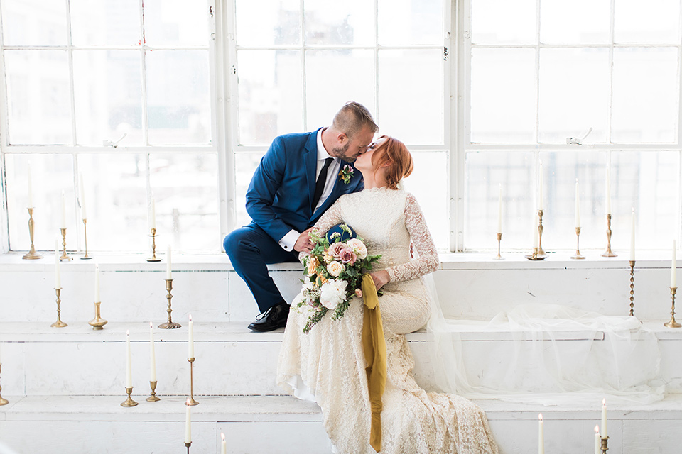 ethereal-shoot-bride-and-groom-kissing-on-white-step-bride-wearing-a-flowing-white-gown-with-a-high-neckline-and-long-sleeves-with-lace-detailing-groom-in-cobalt-blue-suit-with-a-black-long-tie