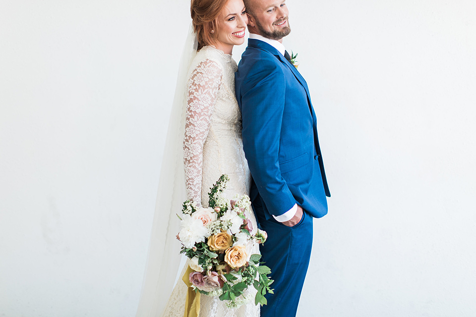 ethereal-shoot-couple-standing-sideways-bride-wearing-a-flowing-white-gown-with-a-high-neckline-and-long-sleeves-with-lace-detailing-groom-in-cobalt-blue-suit-with-a-black-long-tie