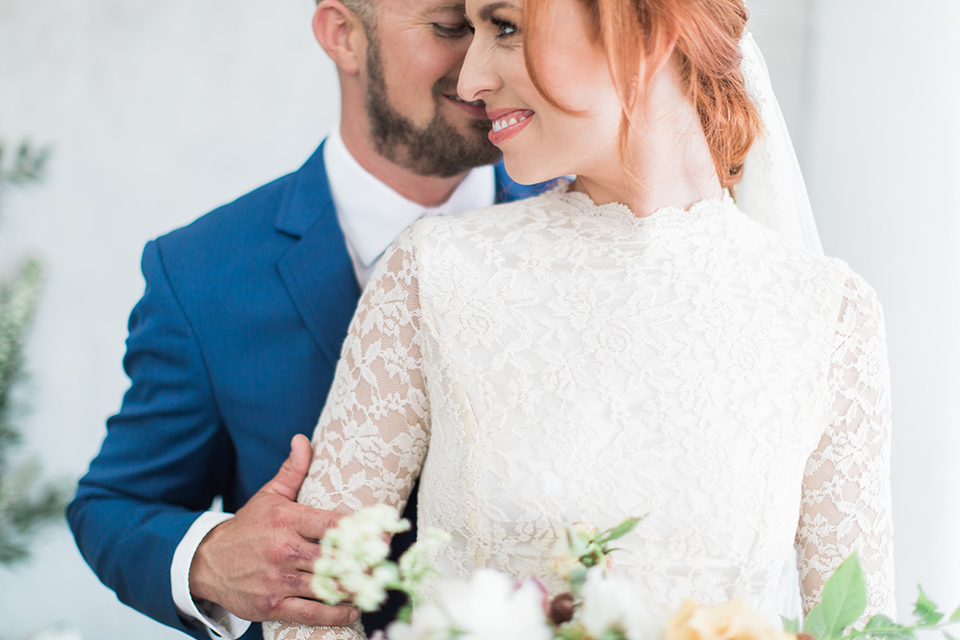 ethereal-shoot-groom-behind-bride-close-up-bride-wearing-a-flowing-white-gown-with-a-high-neckline-and-long-sleeves-with-lace-detailing-groom-in-cobalt-blue-suit-with-a-black-long-tie