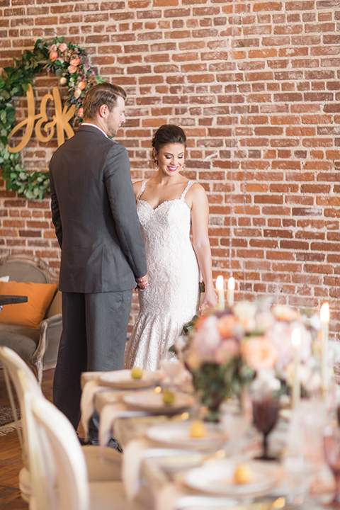 Orange-county-whimsical-wedding-at-franciscan-gardens-bride-and-groom-standing-by-table