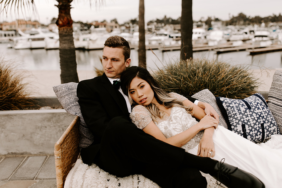 huntington-bay-club-shoot-bride-and-groo-laying-on-the-couch-bride-wearing-a-flowing-gown-with-a-beaded-bodice-and-ca-sleeves-groom-wearing-a-black-suit-with-a-green-velvet-bow-tie