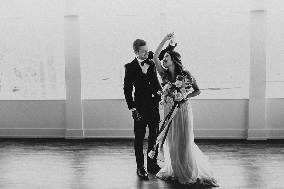 huntington-bay-club-shoot-bride-and-groom-dancing-bride-wearing-a-flowing-gown-with-a-beaded-bodice-and-ca-sleeves-groom-wearing-a-black-suit-with-a-green-velvet-bow-tie