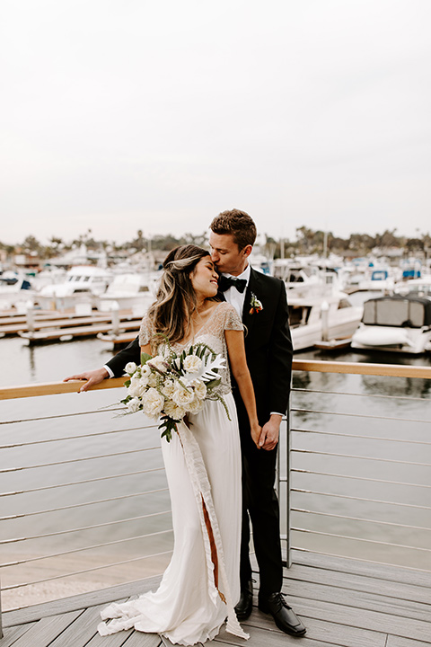 huntington-bay-club-shoot-bride-and-groom-near-the-water-standing-bride-wearing-a-flowing-dress-with-a-beaded-bodice-and-sleeves-groom-wearing-a-black-suit-with-a-green-velvet-bow-tie
