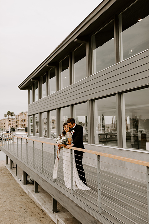 huntington-bay-club-shoot-bride-and-groom-outside-by-metal-awning-bride-wearing-a-flowing-dress-with-a-beaded-bodice-and-sleeves-groom-wearing-a-black-suit-with-a-green-velvet-bow-tie