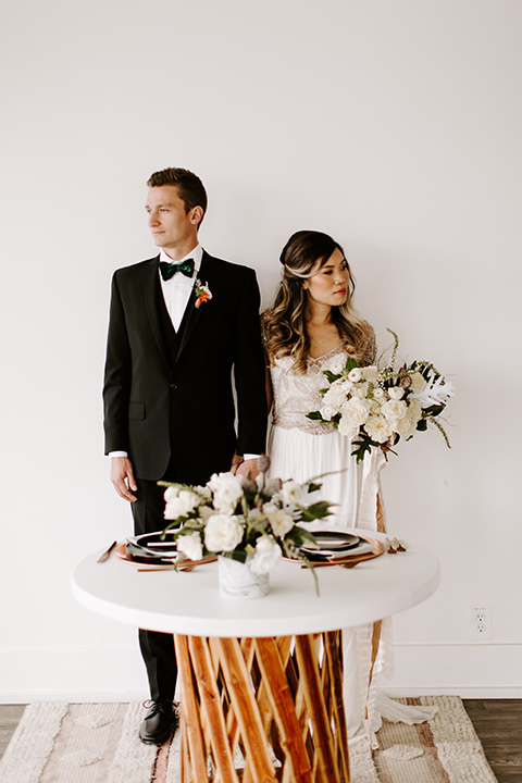 huntington-bay-club-shoot-bride-and-groom-standing-by-table-bride-wearing-a-flowing-dress-with-a-beaded-bodice-and-sleeves-groom-wearing-a-black-suit-with-a-green-velvet-bow-tie