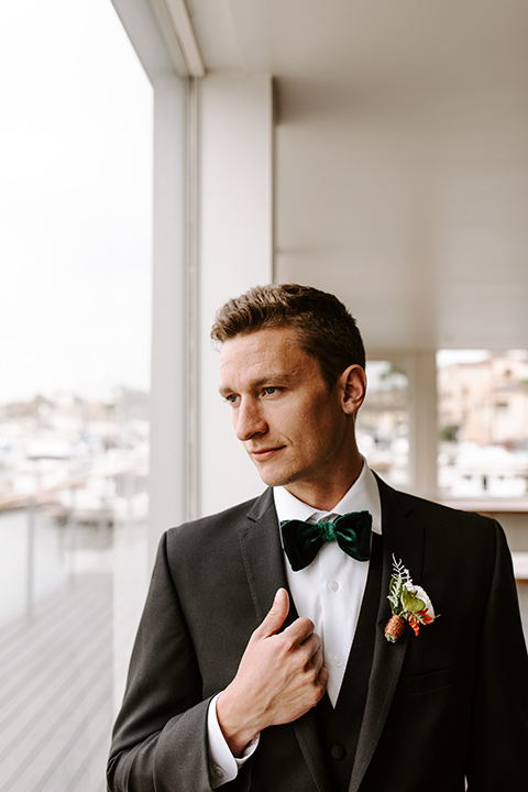 huntington-bay-club-shoot-groom-alone-groom-wearing-a-black-suit-with-a-green-velvet-bow-tie