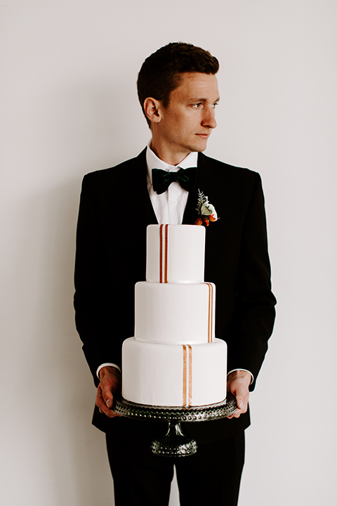 huntington-bay-club-shoot-groom-holding-cake-groom-wearing-a-black-suit-with-a-green-velvet-bow-tie