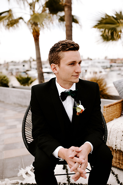 huntington-bay-club-shoot-groom-siting-groom-wearing-a-black-suit-with-a-green-velvet-bow-tie