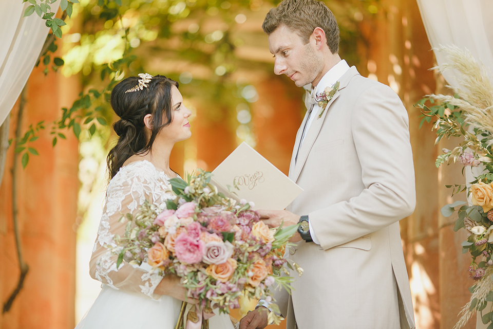Temecula-outdoor-romantic-wedding-at-humphreys-estate-bride-and-groom-ceremony-standing-reading-vows