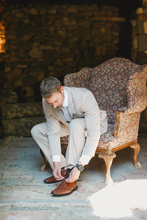 Temecula-outdoor-romantic-wedding-at-humphreys-estate-groom-tan-suit-getting-ready-tying-shoes