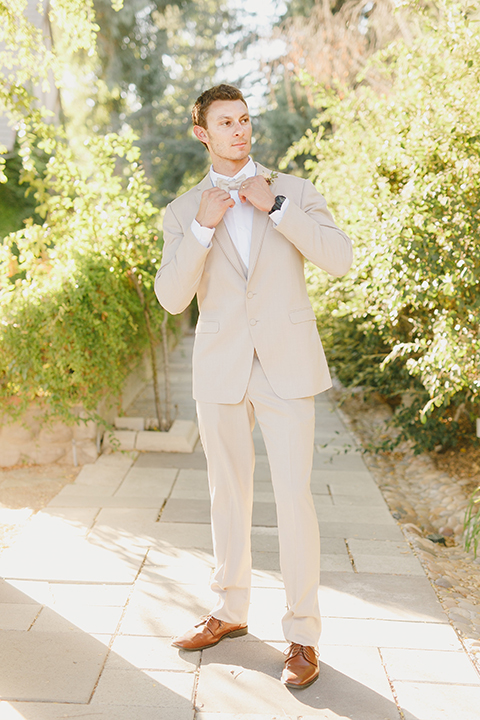 Temecula-outdoor-romantic-wedding-at-humphreys-estate-groom-tan-suit-standing-fixing-bow-tie