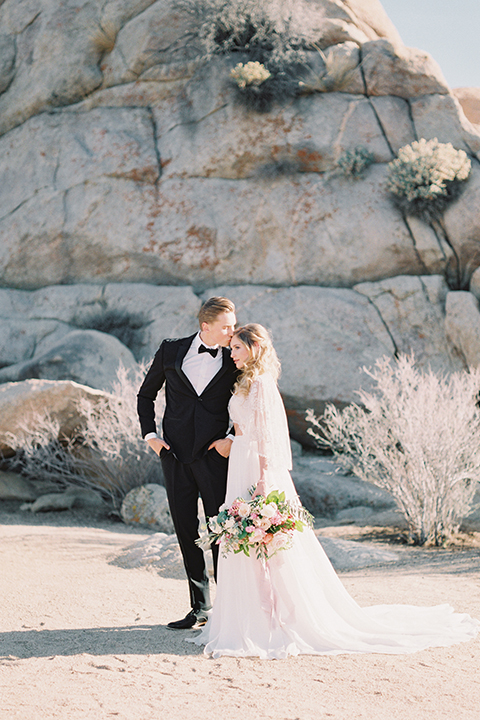 Joshua-tree-wedding-shoot-at-the-ruin-venue-bride-and-groom-holding-hands-and-kissing
