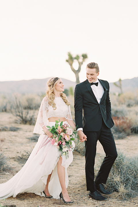 Joshua-tree-wedding-shoot-at-the-ruin-venue-bride-and-groom-holding-hands-and-walking-smiling