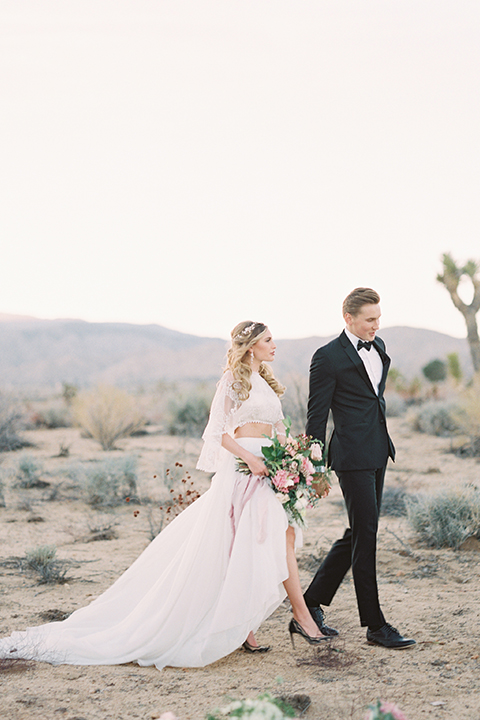 Joshua-tree-wedding-shoot-at-the-ruin-venue-bride-and-groom-holding-hands-and-walking