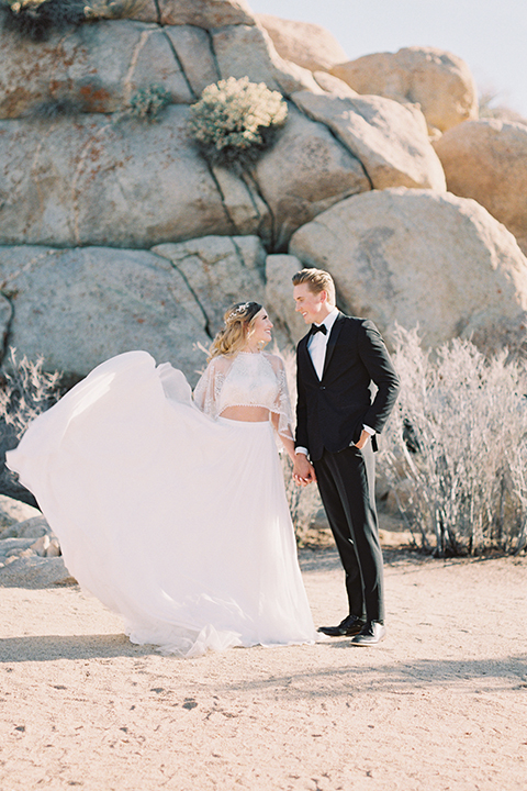 Joshua-tree-wedding-shoot-at-the-ruin-venue-bride-and-groom-holding-hands-bride-holding-dress