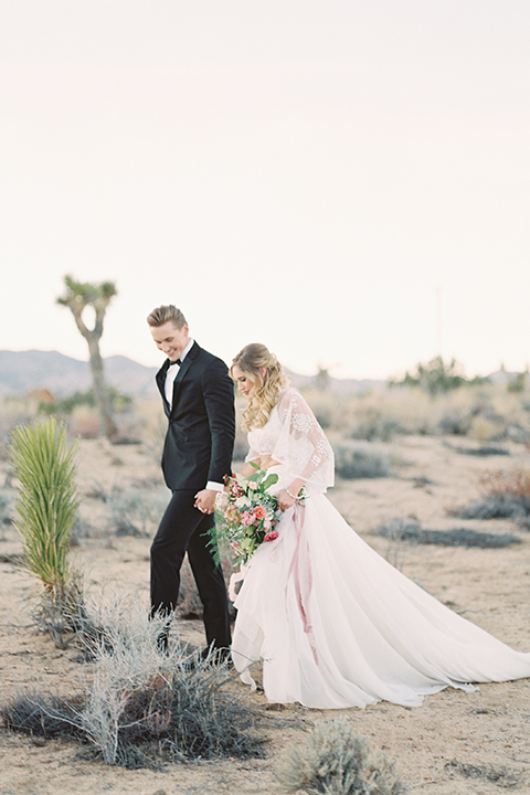 Joshua-tree-wedding-shoot-at-the-ruin-venue-bride-and-groom-standing-holding-hands-and-walking