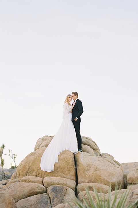 Joshua-tree-wedding-shoot-at-the-ruin-venue-bride-and-groom-standing-on-rocks
