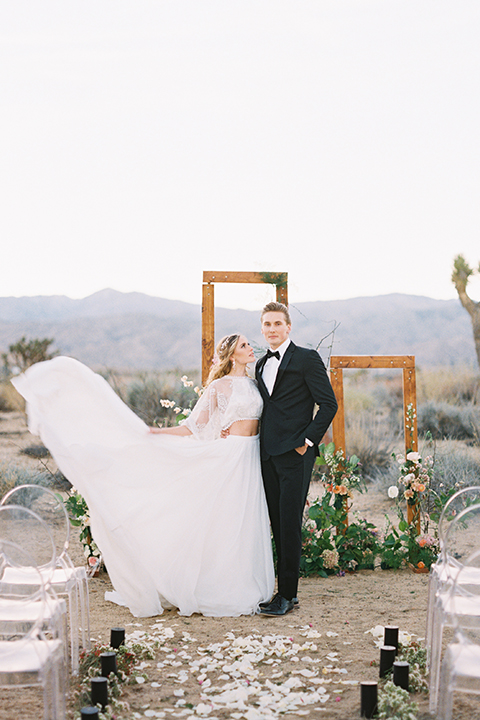 Joshua-tree-wedding-shoot-at-the-ruin-venue-ceremony-bride-and-groom-holding-dress