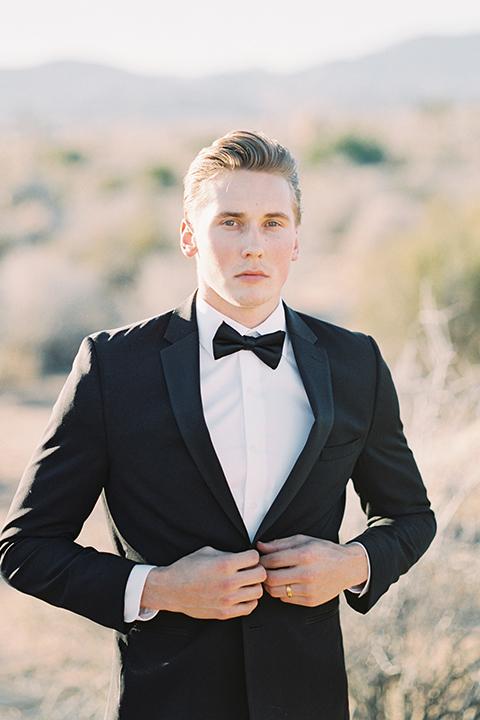 Joshua-tree-wedding-shoot-at-the-ruin-venue-groom-black-tuxedo-holding-coat-buttoning