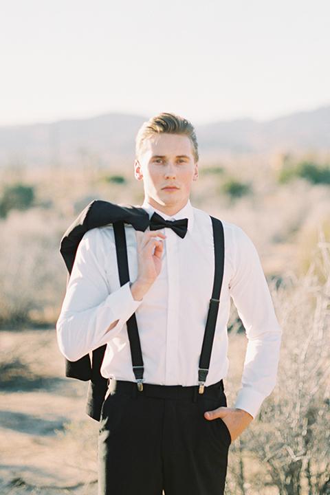 Joshua-tree-wedding-shoot-at-the-ruin-venue-groom-black-tuxedo-holding-coat-over-shoulders