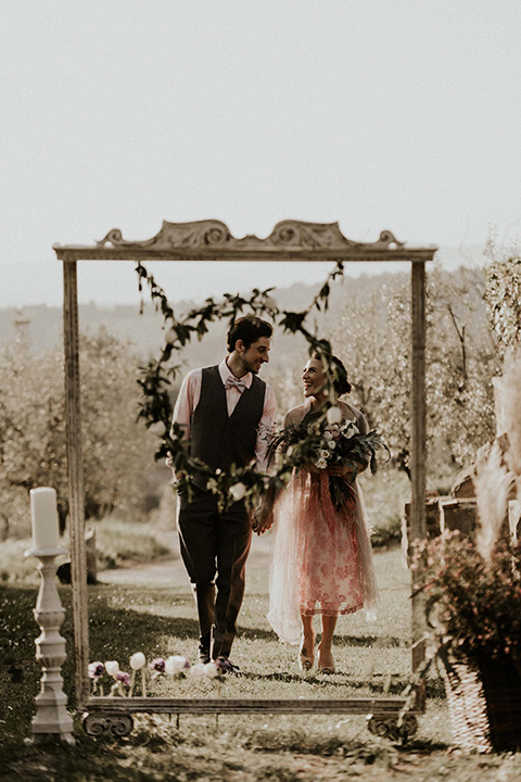 la-dolce-vita-bride-and-groom-at-ceremony-bride-wearing-a-pink-colored-dress-with-lace-detailing-groom-in-grey-pants-and-a-grey-vest