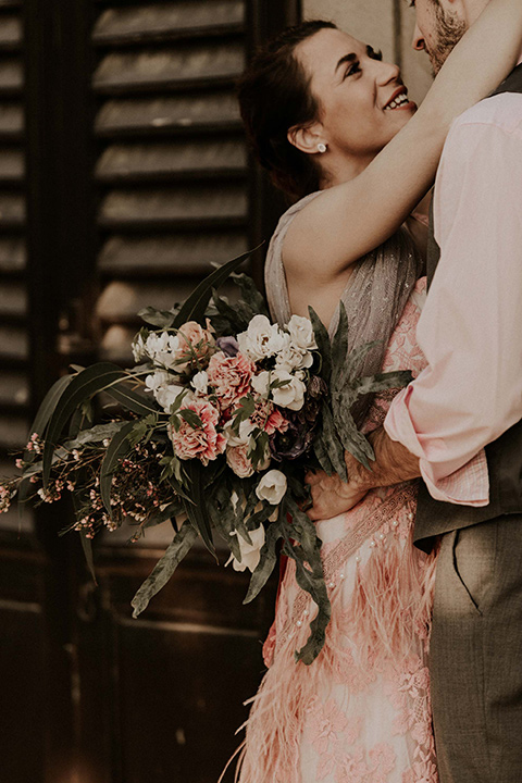la-dolce-vita-bride-and-groom-holding-each-other-laughing-bride-wearing-a-pink-colored-dress-with-lace-detailing-groom-in-grey-pants-and-a-grey-vest