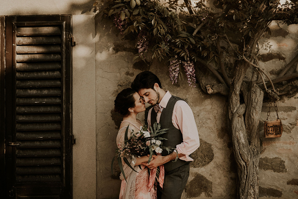 la-dolce-vita-bride-and-groom-under-the-tree-bride-in-a-pink-colored-dress-with-lace-detailing-groom-in-grey-suit-pants-and-vest
