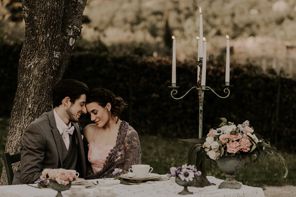 la-dolce-vita-shoot-bride-and-groom-at-sweetheart-table-bride-in-a-pink-colored-dress-with-lace-detailing-groom-in-grey-suit-pants-and-vest