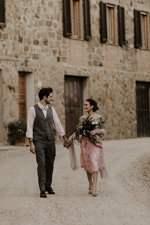la-dolce-vita-shoot-bride-and-groom-on-the-cobblestone-path-bride-wearing-a-pink-colored-dress-with-lace-detailing-groom-in-grey-pants-and-a-grey-vest