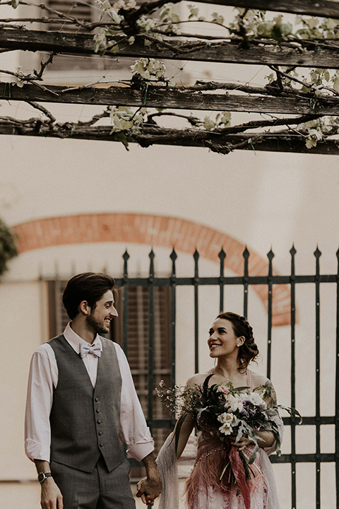 la-dolce-vita-shoot-bride-and-groom-walking-bride-wearing-a-pink-colored-dress-with-lace-detailing-groom-in-grey-pants-and-a-grey-vest