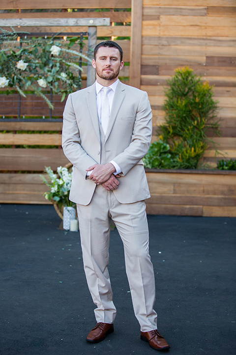 Lot-8-groom-standing-hands-in-front-of-succulent-wall-with-hands-crossed-in-front-of-him-further-shot