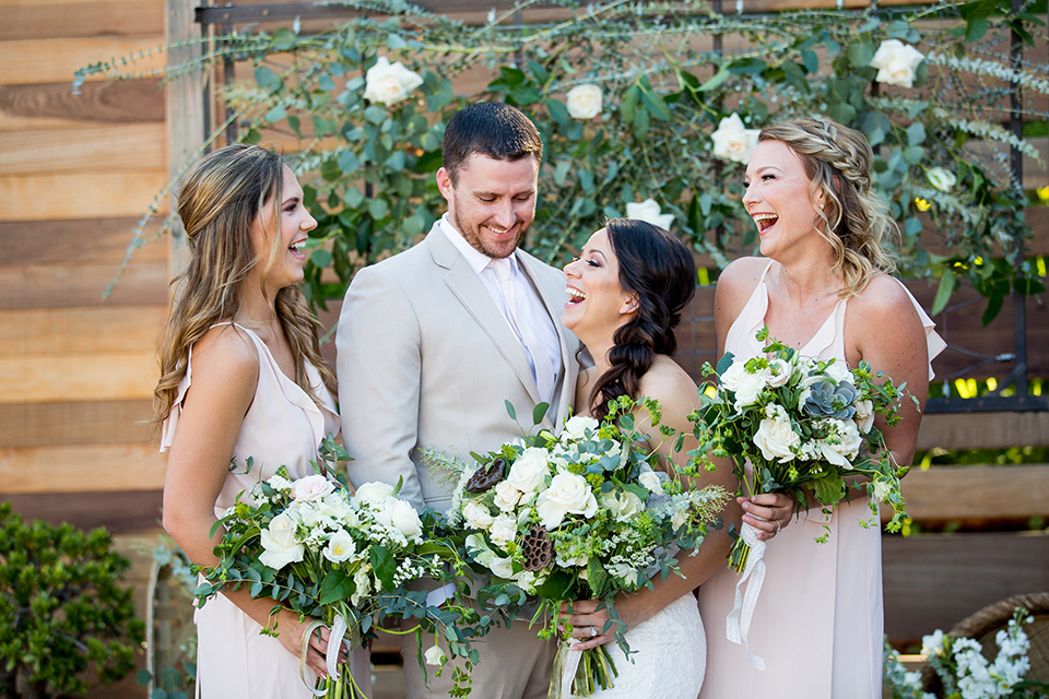 lot-8-bridal-party-laughing-bride-wearing-a-strapless-white-gown-with-lave-groom-in-a-light-grey-suit-with-silver-tie-braideamaids-in-blush-dresses-holding-floral-bouquets-and-all-laughing