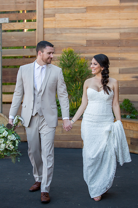 lot-8-bride-and-groom-walking-holding-hands-bride-wearing-a-white-strapless-bridal-gown-with-lace-embellishments-hair-in-a-loose-braid-groom-wearing-a-light-grey-suit-with-a-silver-tie-and-light-brown-shoes