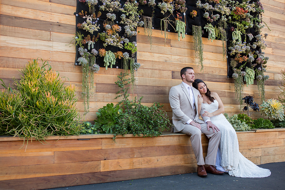 lot-8-bride-and-groom-with-succulent-wall-bride-wearing-a-white-strapless-bridal-gown-with-lace-embellishments-hair-in-a-loose-braid-groom-wearing-a-light-grey-suit-with-a-silver-tie-and-light-brown-shoes