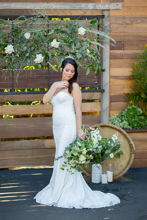 lot-8-bride-looking-over-her-shoulder-bride-wearing-a-white-strapless-bridal-gown-with-lace-embellishments-hair-in-a-loose-braid-holding-a-big-floral-bouquet