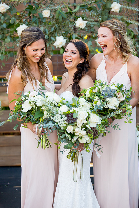 lot-8-bride-with-maids- bride-wearing-a-strapless-white-gown-with-and-loose-braid-while-braideamaids-are-in-blush-dresses-holding-floral-bouquets-and-all-laughing